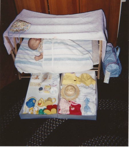 Caitlin in a crib I constructed for her, with her accesseries underneath